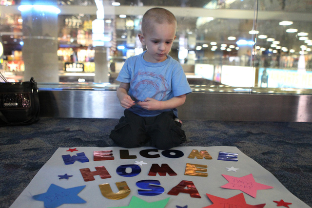Kaiden Cherry, 3, decorates his poster for a flag-waving homecoming event for 28 World War II veterans at McCarran International Airport in Las Vegas Sunday, April 19, 2015. The veterans returned  ...