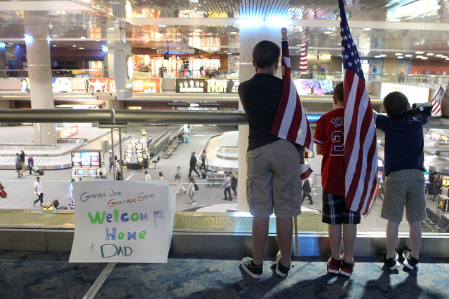 Children wait for a flag-waving homecoming event for 28 World War II veterans at McCarran International Airport in Las Vegas Sunday, April 19, 2015. The veterans returned from a trip to see war me ...