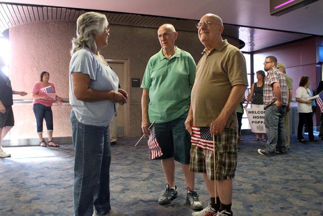 Friends from left, Karen Doherty, Orrin Baisden, and Bernie Stallard, wait during a flag-waving homecoming event for 28 World War II veterans at McCarran International Airport in Las Vegas Sunday, ...