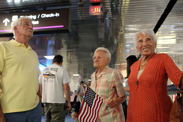 David Morgan, from left, with his wife Jeniece, and Olga Genzoe, wait for Genzoe's brother Nicholas Speranza, 94, during a flag-waving homecoming event for 28 World War II veterans at McCarran Int ...