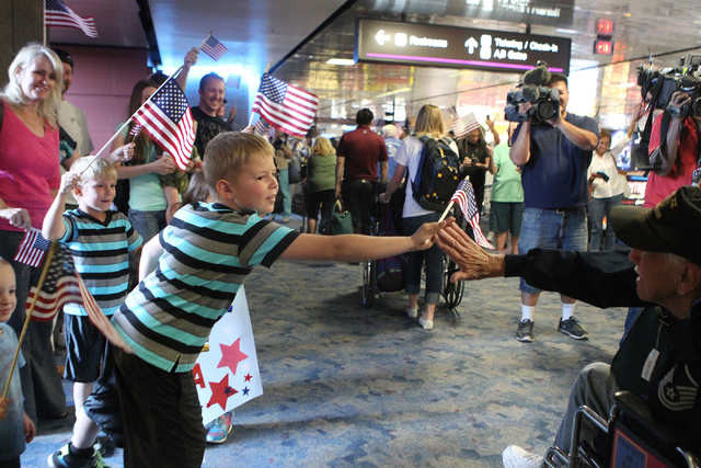 Tyler Ludlow, 9, high fives his great grandfather and World War II veteran Ted Dobrich, 87, during a flag-waving homecoming event for 28 World War II veterans at McCarran International Airport in  ...