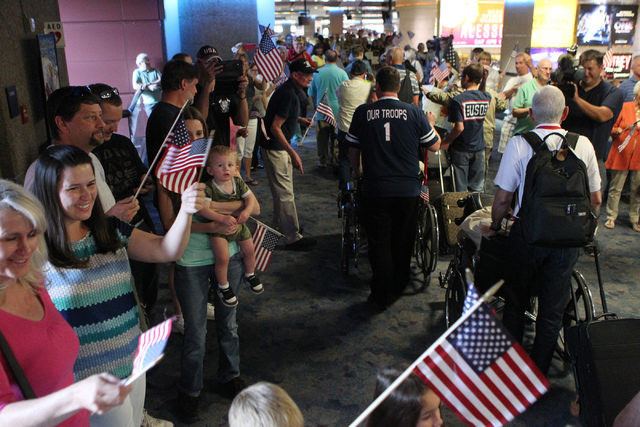 People cheer at the arrival of 28 World War II veterans for a flag-waving homecoming event at McCarran International Airport in Las Vegas Sunday, April 19, 2015. The veterans returned from a trip  ...