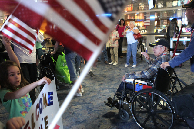 World War II veteran Joe Rogers waves as he is welcomed during a flag-waving homecoming event for 28 World War II veterans at McCarran International Airport in Las Vegas Sunday, April 19, 2015. Ro ...