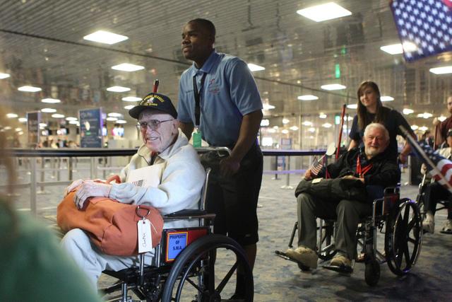World War II veterans Chet Spiewak, 92, left, and John Schleppegrell, 89, are wheeled to a flag-waving homecoming event for 28 World War II veterans at McCarran International Airport in Las Vegas  ...