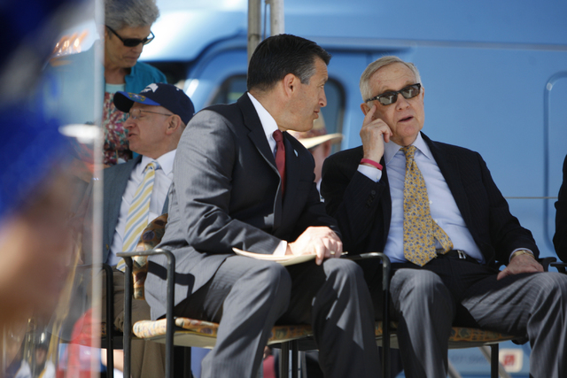 Nevada Gov. Brian Sandoval, left, speaks with U.S. Sen. Harry Reid, D,Nev., during the ground breaking ceremony for the I-11 Boulder City bypass project in Boulder City, Nev., Monday, April 6, 201 ...