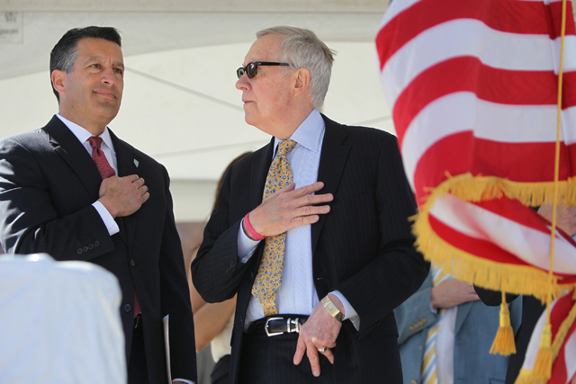 Nevada Gov. Brian Sandoval, left, and U.S. Sen. Harry Reid, D,Nev., recite the Pledge of Allegiance during the ground breaking ceremony for the I-11 Boulder City bypass project in Boulder City, Ne ...