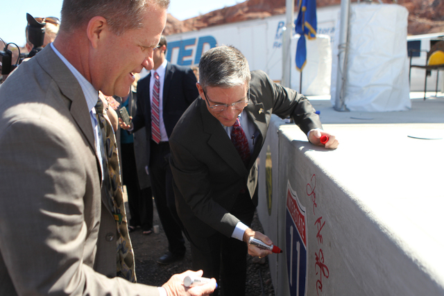 Nevada Lt. Gov. Mark Hutchinson, left, waits for U.S. Rep. Joe Heck, R-Nev., to sign a concrete box culvert during the ground breaking ceremony for the I-11 Boulder City bypass project in Boulder  ...