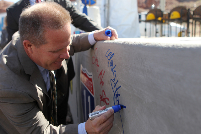 Nevada Lt. Gov. Mark Hutchinson signs a concrete box culvert during the ground breaking ceremony for the I-11 Boulder City bypass project in Boulder City, Nev., Monday, April 6, 2015. (Erik Verduz ...