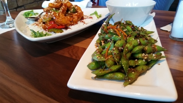 Wok-Fired Calamari & Brown Rice, left, and Togarashi Edamame Beans, both popular menu items, are shown at Lazy Dog Restaurant. (Lisa Valentine/View)