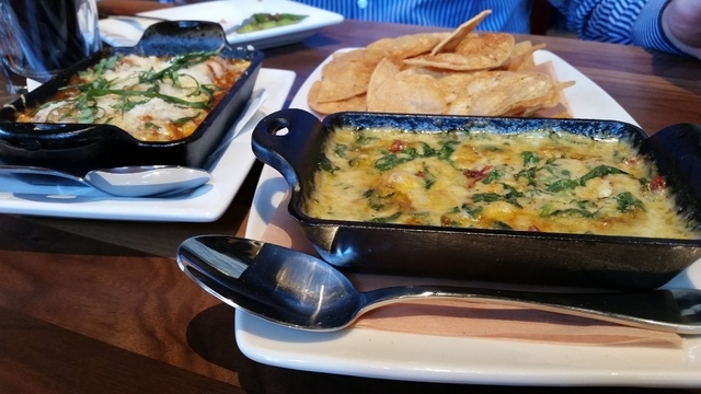 Brick Oven Spinach & Sundried Tomato Cheese Dip with hand-cut corn tortilla chips, front, is shown at Lazy Dog, with Sicilian Turkey Meatballs behind it. (Lisa Valentine/View)
