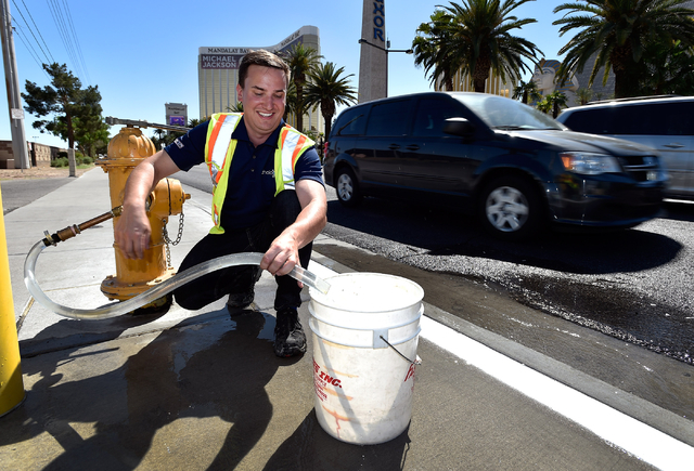 Michael Belluz, with Echologics Engineering, runs water from a fire hydrant to simulate a water leak along the Strip in Las Vegas on Monday, April 13, 2015.  The water district recently upgraded t ...