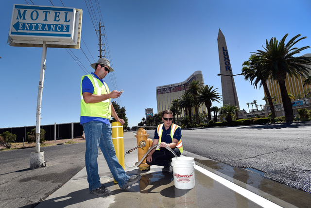 Ryan Benner, left, with the Las Vegas Valley Water District, and Michael Belluz, with Echologics Engineering, run water from a fire hydrant to simulate a water leak along the Strip in Las Vegas on ...
