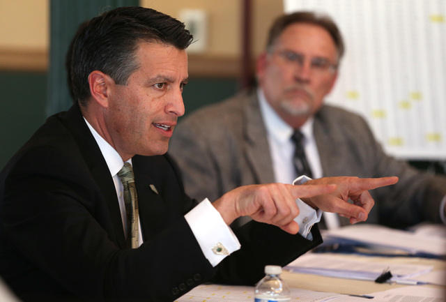 Gov. Brian Sandoval answers media questions about his proposed business license fee at the Capitol in Carson City, Nev., on Thursday, Jan. 29, 2015. Sandoval's Chief of Staff Mike Willden is at ri ...