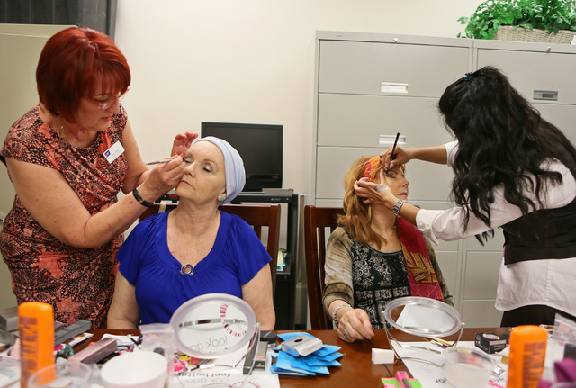 Volunteers Linda Gilbert, far left, and Lia Yulianti, far right, apply makeup to participants Christine Hernandez, center left, and Jan Lewellyn, center right, during a Look Good Feel Better class ...