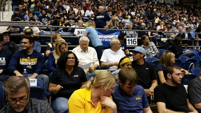 Arizona coaching legend Lute Olson, center of the crowd in striped shirt, checks the stat sheet with his wife, Kelly, at the Walkup Skydome in Flagstaff, Ariz., on March 31, 2015. Olson came to su ...