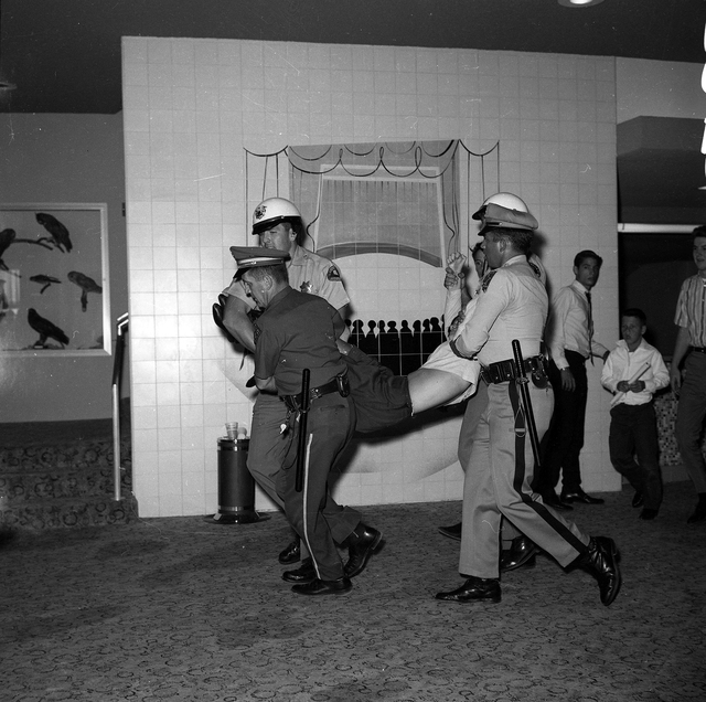 Police carry a young girl who fainted while The Beatles performed on stage at the Las Vegas Convention Center on Aug. 20, 1964. (Courtesy Photo/Las Vegas Convention and Visitors Authority)
