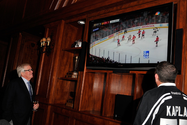 Bill Foley, left, the public face of an ownership group seeking to create an NHL team in Las Vegas, watches a hockey news report during a promotional stop to sell hockey tickets at the Southern Hi ...