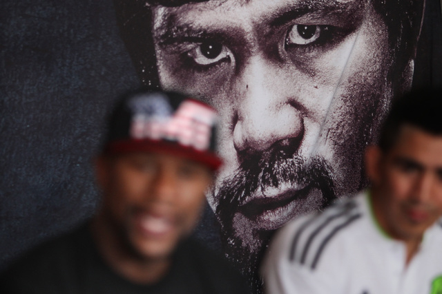 A poster featuring Manny Pacquiao looms over Floyd Mayweather during his news conference Tuesday, April 14, 2015, in advance of his May 2nd fight against Manny Pacquiao. (Sam Morris/Las Vegas Revi ...