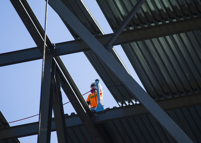 A worker stands on the roof of the MGM Resorts International-AEG arena  behind New York-New York casino-hotel Monday, March 30, 2015. The $375 million arena is scheduled to open in April 2016. (Je ...