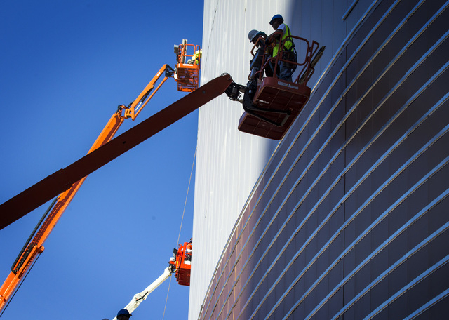 Workers place the outer siding at the  MGM Resorts International-AEG arena construction site behind New York-New York casino-hotel is seen Monday, March 30, 2015. The $375 million arena is schedul ...