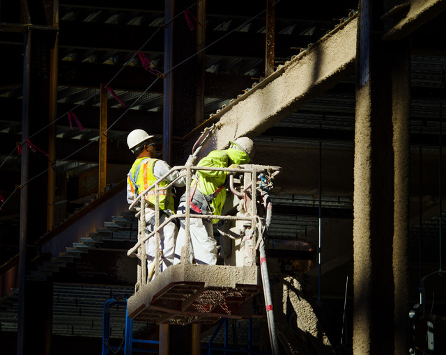 Workers spray heat retardant at the MGM Resorts International-AEG arena construction site behind New York-New York casino-hotel Monday, March 30, 2015. The $375 million arena is scheduled to open  ...
