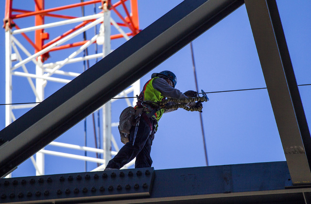An ironwork walks on a beam at the MGM Resorts International-AEG arena construction site behind New York-New York casino-hotel Monday, March 30, 2015. The $375 million arena is scheduled to open i ...