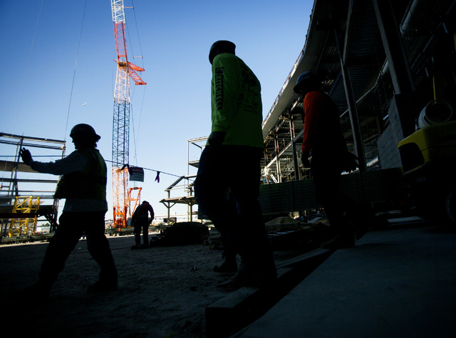 Workers are silhouetted while working at the MGM Resorts International-AEG arena construction site behind New York-New York casino-hotel on Monday, March 30, 2015. The $375 million arena is schedu ...