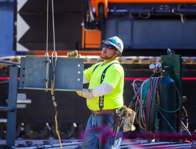 A worker guides a beam at  the MGM Resorts International-AEG arena construction site behind New York-New York casino-hotel Monday, March 30, 2015. The $375 million arena is scheduled to open in Ap ...