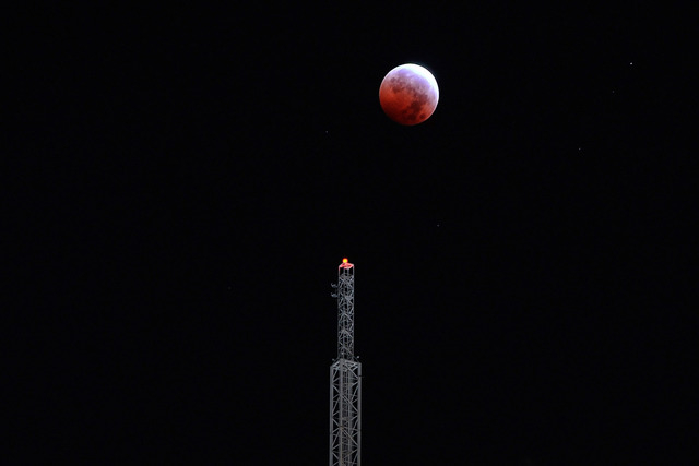 "A total lunar eclipse or ""blood moon"" appears above the Stratosphere Tower on early Wednesday, Oct. 8, 2014, in Las Vegas. (David Becker/Las Vegas Review-Journal)"