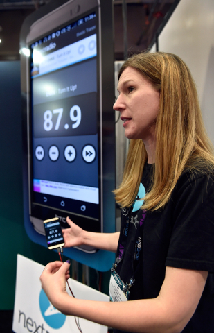 AJ Rudolph with NextRadio displays a mobile phone with her company's application open at the National Association of Broadcasters show at the Las Vegas Convention Center on Tuesday, April 14, 2015 ...