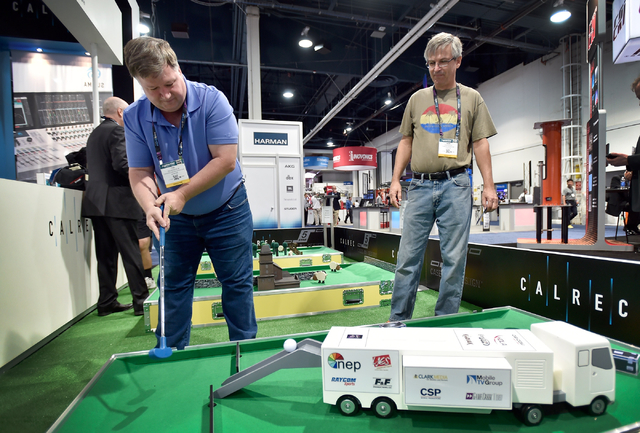 Ted Benson and Reini Blech play miniature golf at the Calrec booth during the National Association of Broadcasters show at the Las Vegas Convention Center on Tuesday, April 14, 2015, in Las Vegas. ...