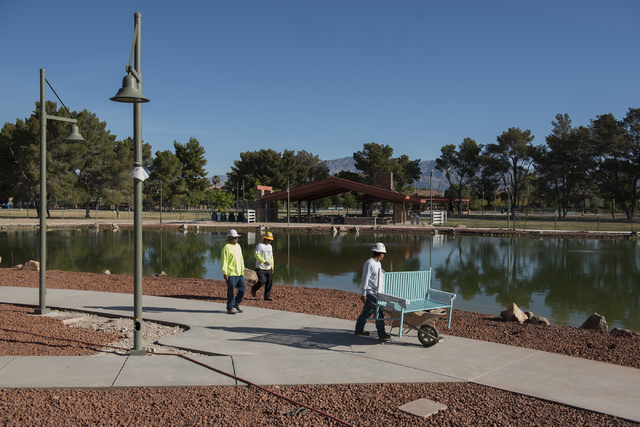 Construction workers move a bench at a new lake behind the amphitheater site at Craig Ranch Regional Park in North Las Vegas on Wednesday, April 29, 2015. October 2015 is the estimated grand openi ...