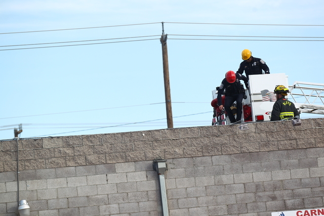 The North Las Vegas Fire Department assisted North Las Vegas police by lifting officers onto the roof of a business Tuesday morning, April 14, 2015. Police are investigating a shooting in the 2500 ...