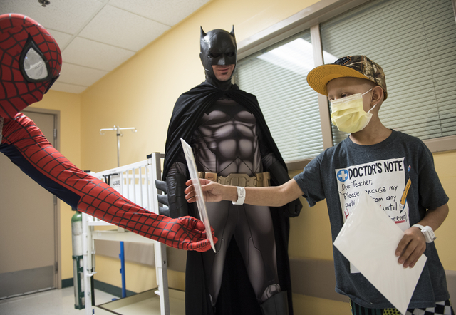 Volunteers from the non-profit organization Critical Care Comics from left, Michael Mutzhaus, dressed as Spiderman and Cody Strohl, dressed as Las Vegas Batman, offer free comics to sick and injur ...