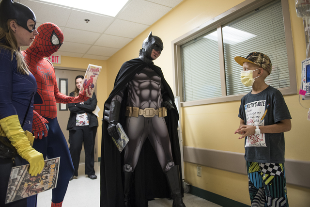 Volunteers from the non-profit organization Critical Care Comics from left, Jessica Miller, dressed as Batgirl, Michael Mutzhaus, dressed as Spiderman and Cody Strohl, dressed as Las Vegas Batman, ...