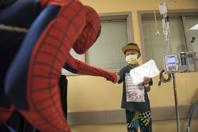 Volunteer Michael Mutzhaus, dressed as Spiderman, bumps fists with Juan Ballesteros, 9. Mutzhaus and other volunteers from the non-profit organization Critical Care Comics brought free comics to s ...