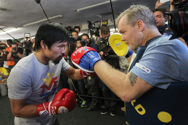Manny Pacquiao hits pads with trainer Freddie Roach during his media workout Wednesday, April 15, 2015, at Freddy Roach's Wild Card Gym in Los Angeles. Pacquiao faces Floyd Mayweather in a welterw ...