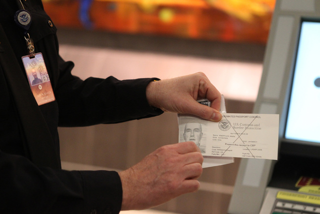Port Director for U.S. Customs and Border Protection Warren Eales shows a receipt people receive after using one of the newly installed Automated Passport Control kiosks at the U.S. Customs Arriva ...