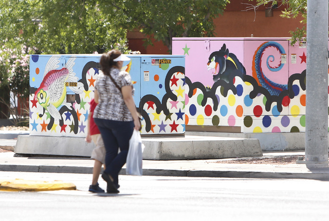 Pedestrians walk past utility boxes painted by local artists at the corner of Desert Inn Road and Maryland Parkway on Thursday, April 30, 2015. The boxes and others on Maryland Parkway were painte ...