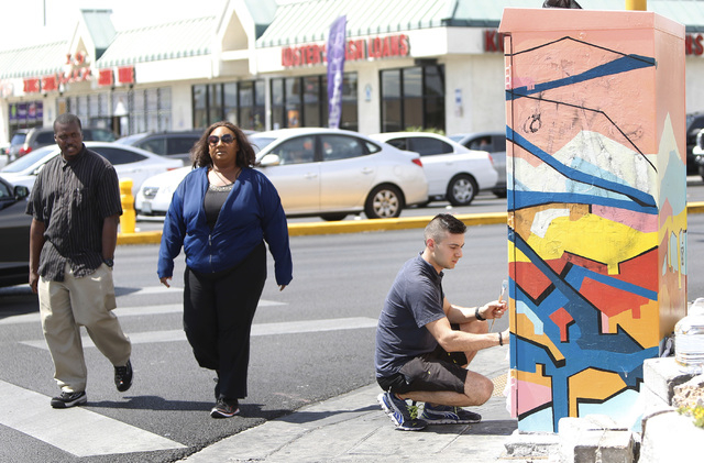 Pedestrians walk past artist Valentin Yordanov as he covers up graffiti on a utility box at the corner of Desert Inn Road and Maryland Parkway on Thursday, April 30, 2015. The box and others on Ma ...