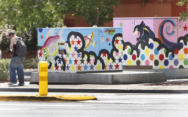 A pedestrian walks past utility boxes painted by local artists at the corner of Desert Inn Road and Maryland Parkway on Thursday, April 30, 2015. The boxes and others on Maryland Parkway were pain ...