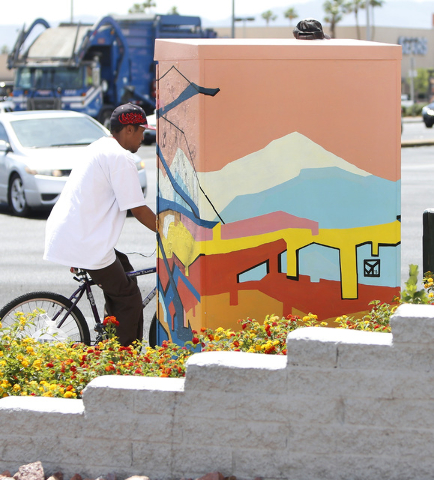 A cyclist rides past a utility box painted by a local artist at the corner of Desert Inn Road and Maryland Parkway on Thursday, April 30, 2015. The boxes and others on Maryland Parkway were painte ...