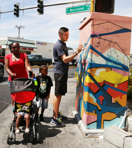 Pedestrians walk past artist Valentin Yordanov as he covers up graffiti on a utility box at the corner of Desert Inn Road and Maryland Parkway on Thursday, April 30, 2015. The box and nine others  ...