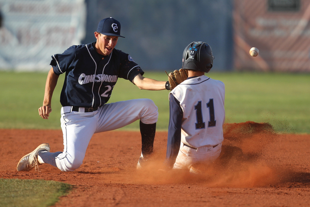 Centennial's Tanner Wright (11) slides safely to second base after a missed catch by Chatsworth's Sam Shaikin (23) in their baseball game at Centennial High School in Las Vegas Wednesday, April 1, ...