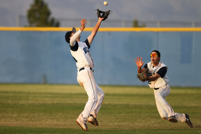 Centennial's Jake Portaro (24), left, makes a catch in the outfield with his teammate Gino Sabey (12) against Chatsworth in their baseball game at Centennial High School in Las Vegas Wednesday, Ap ...