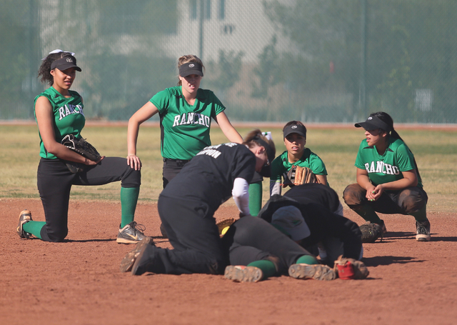 Rancho girls take a knee as injured teammate Tiare Lee, front center, is tended to during a softball game against Coronado at Coronado High School Wednesday, April 8, 2015, in Henderson. Coronado  ...