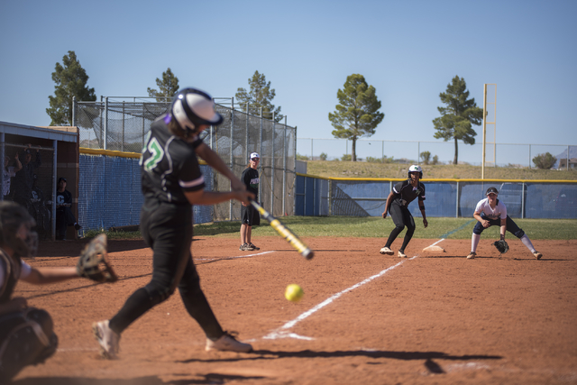 Palo Verde High School's Kali Tomlinson (17) swings at a pitch as Dejanae Gage (2) takes a lead at third base against Centennial High School during their softball game played at Centennial's softb ...