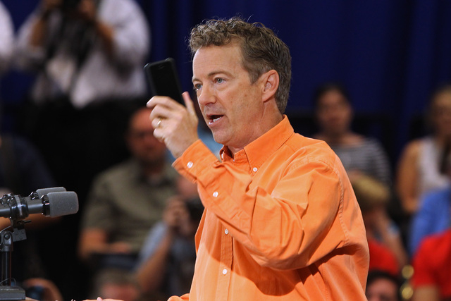 U.S. Sen. Rand Paul, R-Ky., waves a cell phone while speaking out against the federal government's gathering of phone data at a campaign rally in Las Vegas Saturday, April 11, 2015. (Sam Morris/La ...