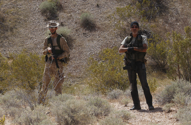 Armed civilians wait nearby as the Bundy family and their supporters gather together under the I-15 highway just outside of Bunkerville in order to confront the BLM and demand the release of their ...