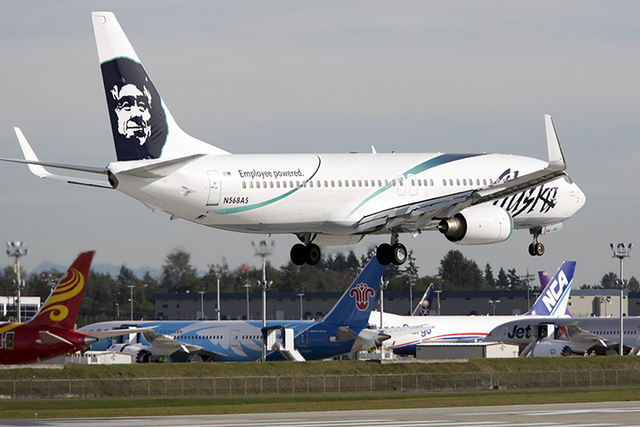 An Alaska Airlines Boeing 737-890 plane lands in front of a row of parked Boeing 787 Dreamliners at Paine Field Airport in Everett, Washington, Oct. 4, 2013. (Jason Redmond/Reuters)